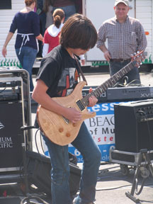 Photo image of Long Beach School of Music guitar student performing at Kids in the Kitchen outdoor fair sponsored by the Junior League of Long Beach